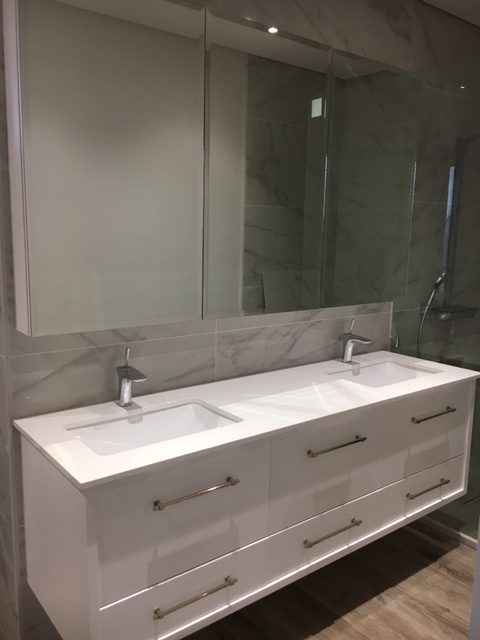 white bathroom cabinet with two taps